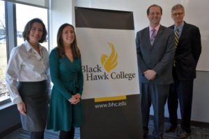 4 people standing in front of Black Hawk College banner