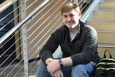 male student sitting on a staircase