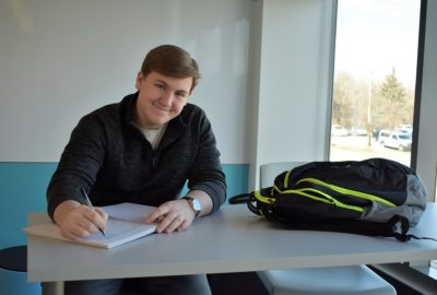 male student sitting at desk writing in a notebook