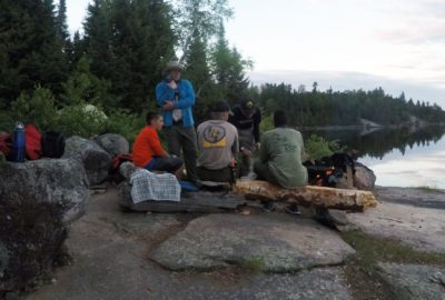 a group of scouts around a campfire on the shore of a lake