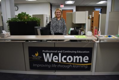 woman standing behind a desk with a welcome sign