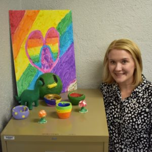 woman standing next to a cabinet displaying children's art