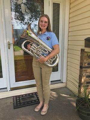 female college student standing & holding euphonium