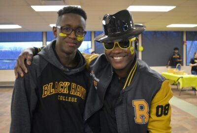 two students wearing black and gold for a Black Hawk College spirit event