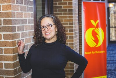 teacher standing next to brick wall with a red banner in the background featuring a logo of hands creating an apple