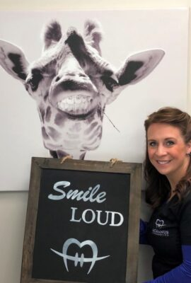 woman holding a Smile LOUD sign with art of a giraffe wearing braces behind her