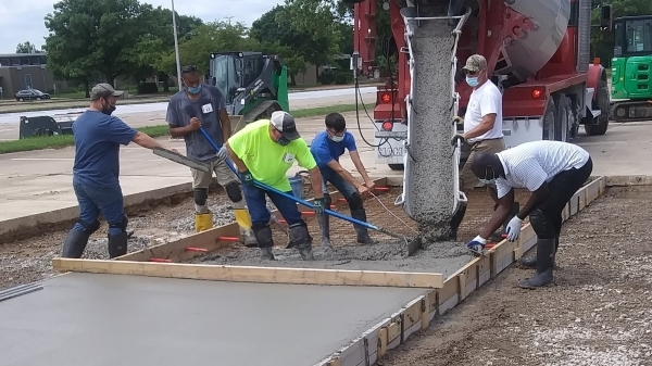 students spreading cement