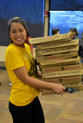 smiling student holding stack of pizza boxes