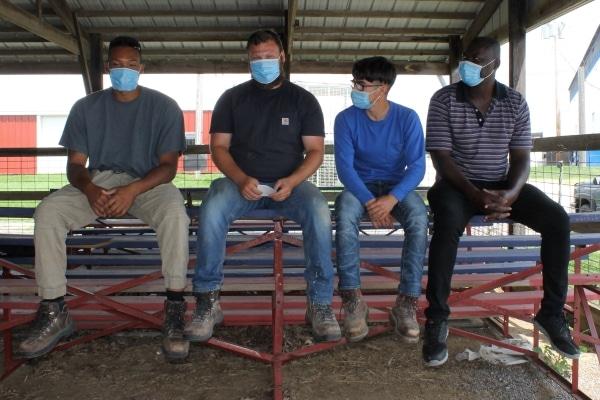 4 people sitting on bleachers wearing masks
