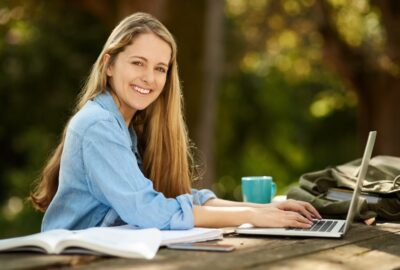 young woman sitting at a table outdoors with a laptop and school supplies