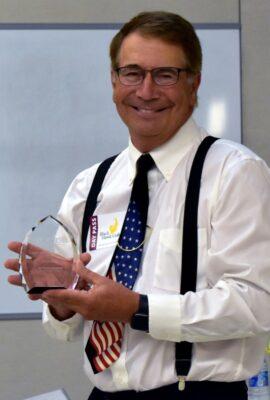 smiling man holding an award