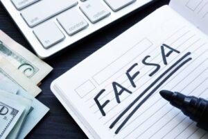 cash, computer keyboard & FAFSA written in notebook