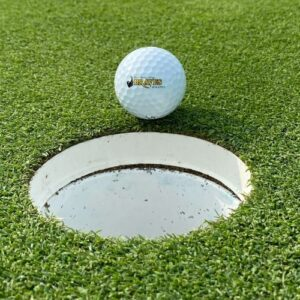 BHC Braves golf ball on edge of cup on the green