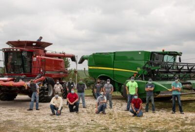 people in masks in front of farming equipment