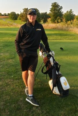 golfer standing with clubs & bag on the green