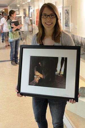 student holding framed art in front of an exhibit