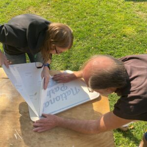 two people working on a sign that reads National Park