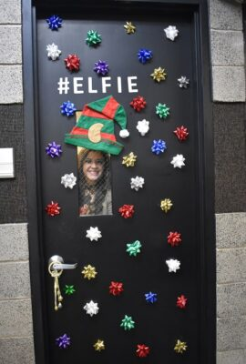 woman looking through window of a door decorated with bows and an elf hat
