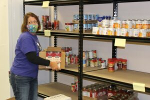 woman holding box of food in front of pantry shelves