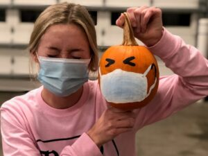 woman wearing mask holding pumpkin painted with mask