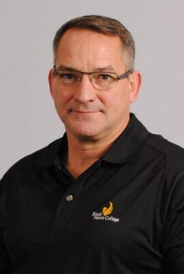 man in black polo shirt with Black Hawk College logo
