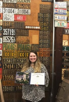 woman holding her degree in front of a wall of license plates