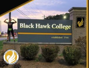 woman standing on the Black Hawk College sign during the Hawk Hustle event