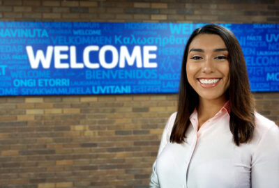 smiling woman in front of a sign that says welcome