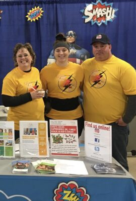woman stands behind an informational table with her daughter and husband