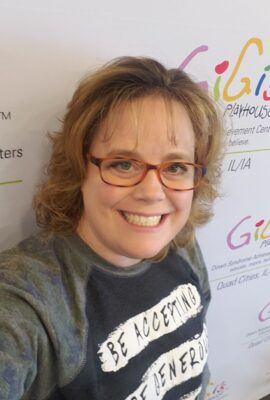 woman smiling with GiGi's Playhouse logos behind her