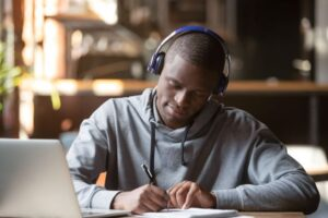 student with headphones & laptop studying