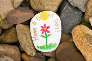 rock painted with flower and Have a great day!