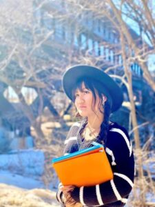 student wearing hat holding binders standing outdoors