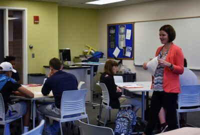 associate professor walking in a classroom with college students at their desks