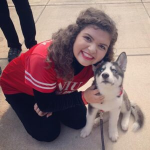 smiling student sitting with a husky puppy