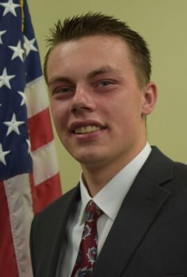Head & shoulders shot of Dillon Sheiss with American flag in background