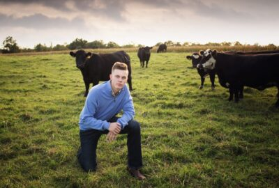 man kneels in a field with cattle in the background