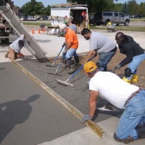 highway construction students spreading cement in parking lot