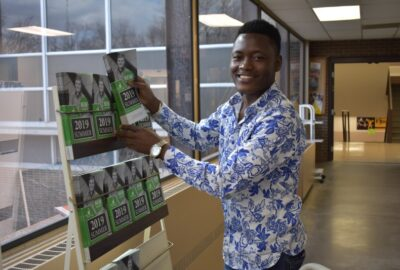 smiling male student placing booklets in a rack