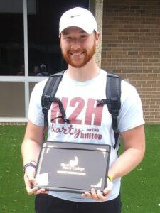 smiling grad outside holding certificate