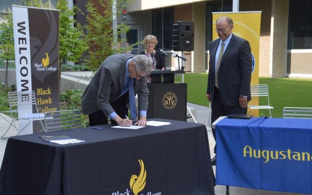 Tim Wynes signing document on table outdoors with 2 people watching and smiling