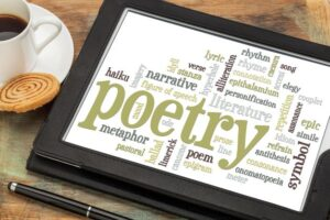 Tablet with words about poetry. Pen & coffee cup next to tablet.