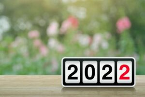 Retro flip clock with 2022 text on wooden table over blurred flowers