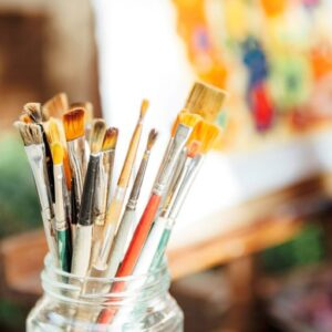 glass jar with paintbrushes in foreground & painting canvas in background