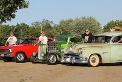 4 car owners standing next to their vintage vehicles